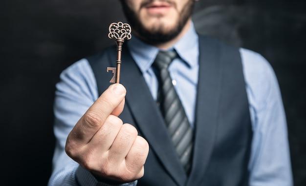 Hombre de negocios, tenencia, llaves, en, mano, en, superficie negra