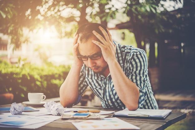 Hombre de negocios tensionado con papeles y gráficos que se sientan en la tabla en el país. empresario con el papeleo y el concepto de plazo.
