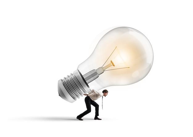 El hombre de negocios tiene una bombilla grande. tener una gran idea para hacer realidad el concepto.