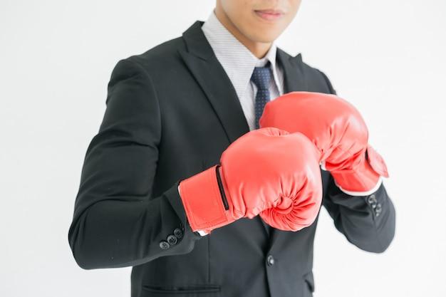 Un hombre de negocios de tipo duro lleva guantes de boxeo.