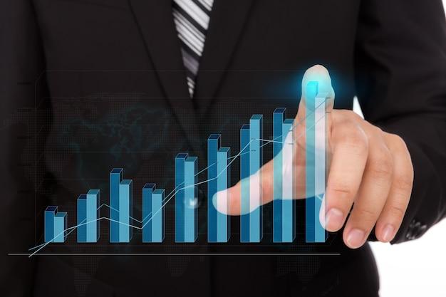 Hombre de negocios tocando la punta de un gráfico de barras