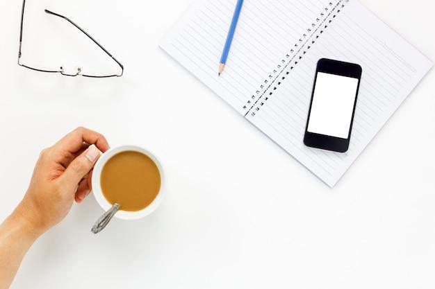 Hombre de negocios tocando la taza de café y teléfono móvil, gafas, café, bloc de notas, lápiz en blanco escritorio de oficina con copia espacio.