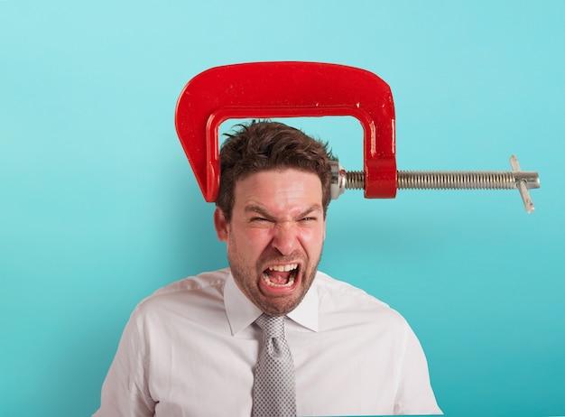 Hombre de negocios con un tornillo de banco en la cabeza. concepto de dolor de cabeza