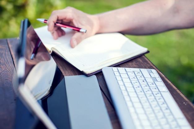 El hombre de negocios trabaja con la computadora portátil y hace registros en el cuaderno al aire libre
