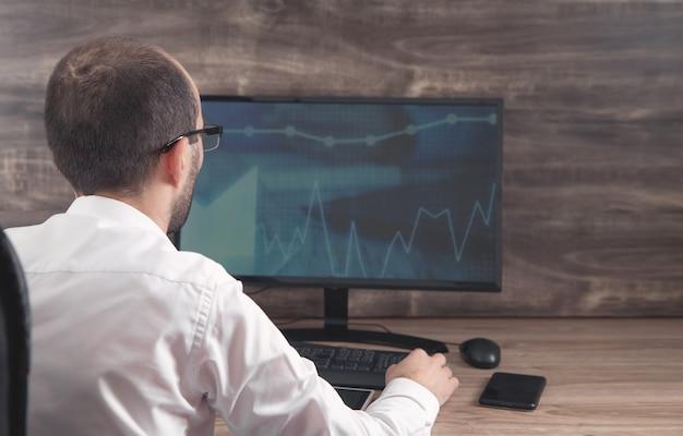 Hombre de negocios trabajando con análisis sentado en el lugar de trabajo con computadora. gráficos y tablas en la pantalla de la computadora. negocio. finanzas. contabilidad