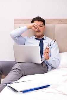Hombre de negocios trabajando en la cama en su casa