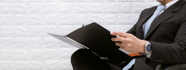 Hombre de negocios trabajando en documentos mirando en una silla