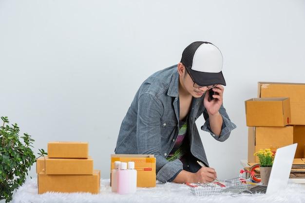 Un hombre de negocios está trabajando en línea para el cliente en el embalaje de la oficina en casa en la pared