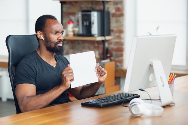 Hombre de negocios trabajando en oficina y sosteniendo carteles en blanco