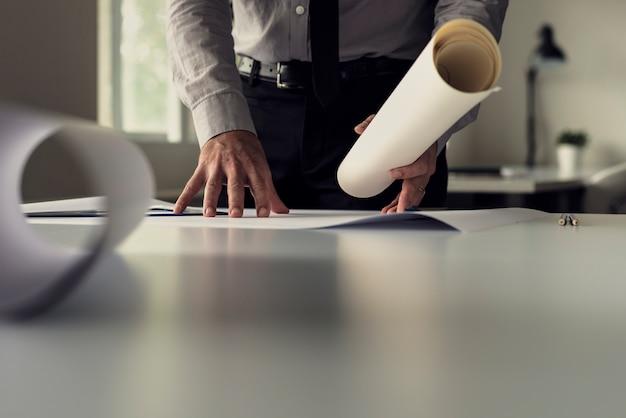 Hombre de negocios trabajando en planos en una oficina en una vista de ángulo bajo