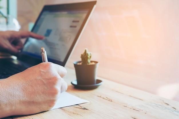 El hombre de negocios está trabajando con su computadora en cafetería