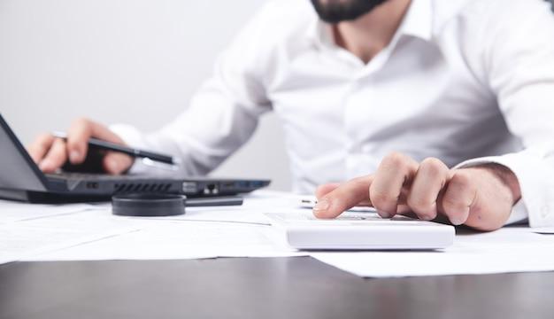 Hombre de negocios trabajando en su computadora portátil y usando la calculadora.