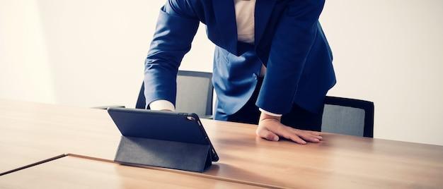 Hombre de negocios trabajando con tableta en sala de seminarios