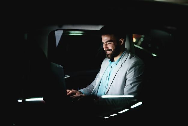 Hombre de negocios trabajando hasta tarde en el coche terminando su trabajo. trabajo duro horas extras conduciendo a casa.