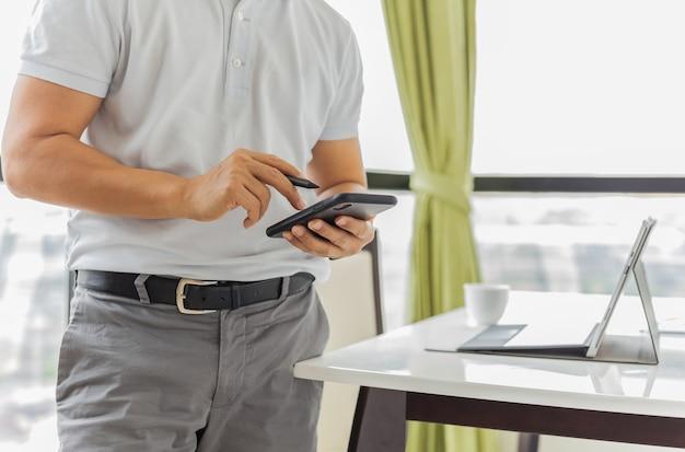 Hombre de negocios trabajando en un teléfono celular con un portátil en la mesa