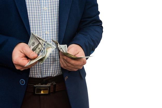 Hombre de negocios en traje con billetes de un dólar estadounidense, aislado en blanco.