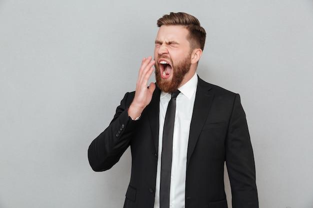 Hombre de negocios en traje bostezando y cubriendo su boca con la mano