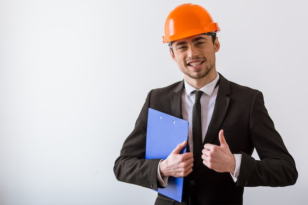Hombre de negocios en traje clásico y casco naranja.