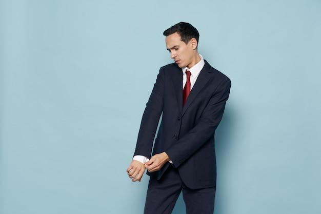 Hombre de negocios en traje clásico endereza la manga de su camisa