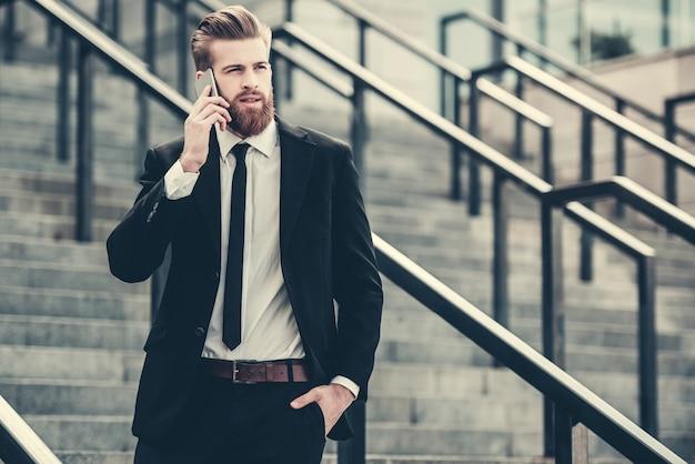 Hombre de negocios en traje clásico está hablando por teléfono móvil.