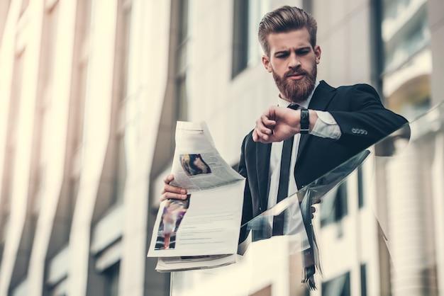 Hombre de negocios en traje clásico está sosteniendo un periódico.