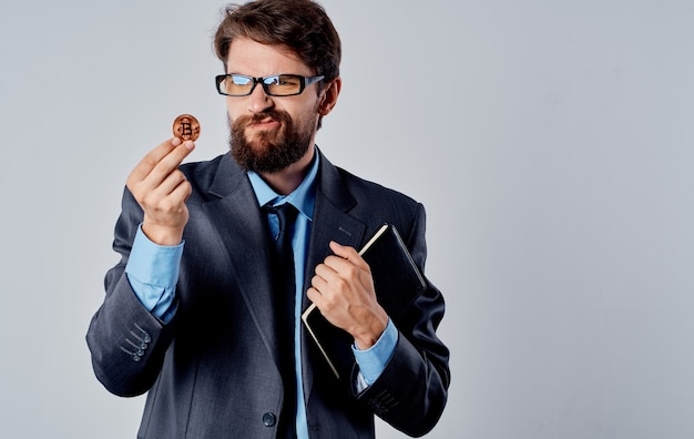 Hombre de negocios en traje con criptomoneda en documentos de moneda bitcoin de mano. foto de alta calidad