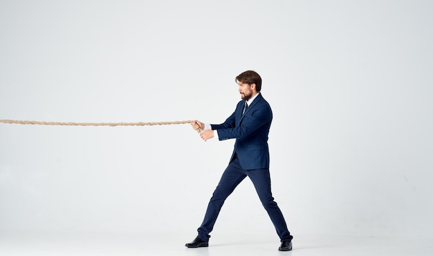 Hombre de negocios en un traje con una cuerda en su fondo claro de la oficina del administrador de las manos