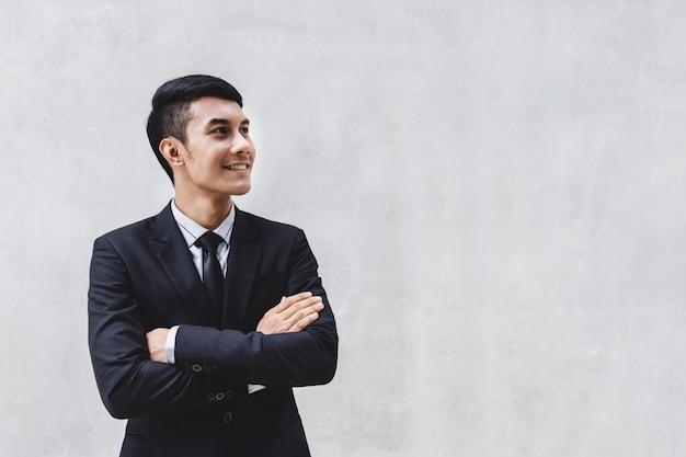 Hombre de negocios en traje formal negro con brazos cruzados