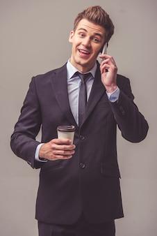 Hombre de negocios en traje está hablando por teléfono móvil