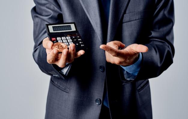 Hombre de negocios en un traje con monedas en sus manos y una calculadora de tipos de cambio