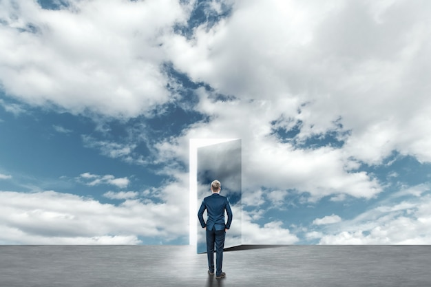 Hombre de negocios en traje de negocios camina a través de una puerta abierta en el cielo