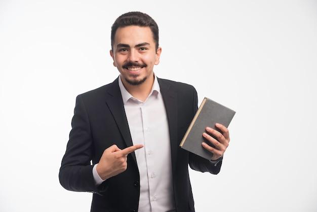 Hombre de negocios en traje negro apuntando a su agenda.