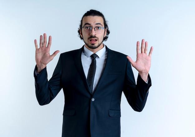 Hombre de negocios en traje negro y gafas levantando los brazos en señal de rendición mirando al frente con expresión de miedo de pie sobre la pared blanca