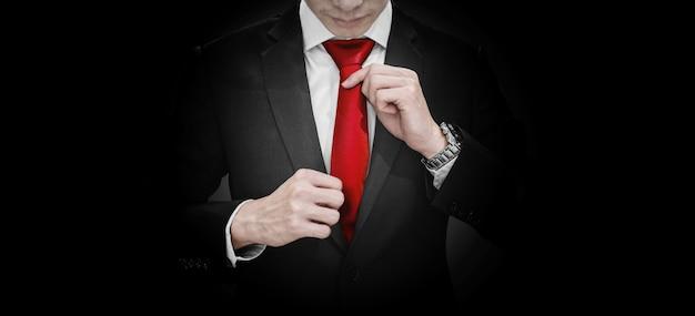 Hombre de negocios en traje negro que ata la corbata roja