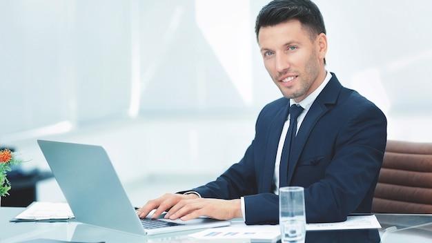 Hombre de negocios en traje negro sentado detrás de un escritorio en la espaciosa oficina y trabajando en el teclado de la computadora portátil