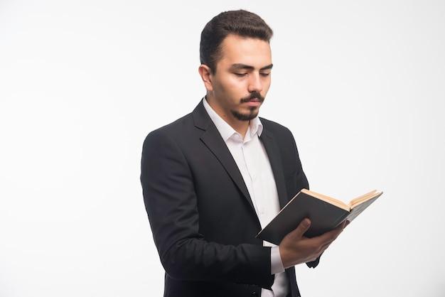 Hombre de negocios en traje negro sosteniendo su lista de tareas y comprobándola.