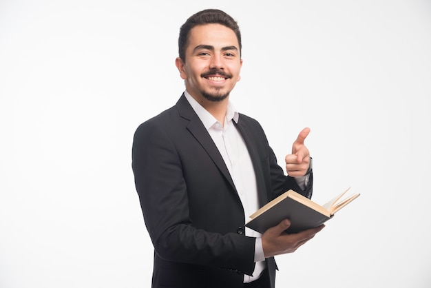 Hombre de negocios en traje negro sosteniendo su lista de tareas y hace pulgar hacia arriba.
