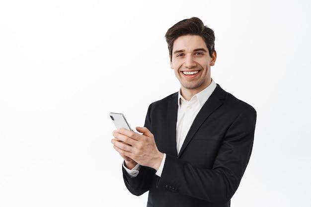 Hombre de negocios en traje negro mediante teléfono móvil, de pie con smartphone y mirando al frente, sonriendo, pared blanca
