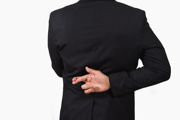 Hombre de negocios en traje oscuro con los dedos cruzados detrás de su espalda