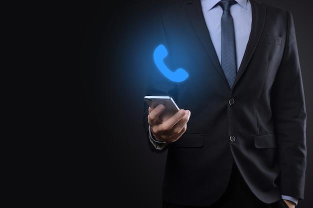 Hombre de negocios, en, traje, en, pared negra, asimiento, teléfono, icon., llamar, ahora, comunicación empresarial, centro de apoyo, servicio, tecnología, concepto.