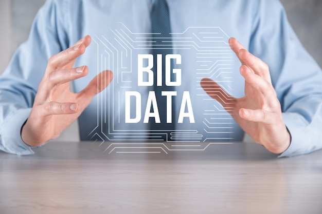 Hombre de negocios con traje en una pared oscura tiene la inscripción big data. concepto de servidor en línea de red de almacenamiento representación de análisis de negocios o redes sociales.