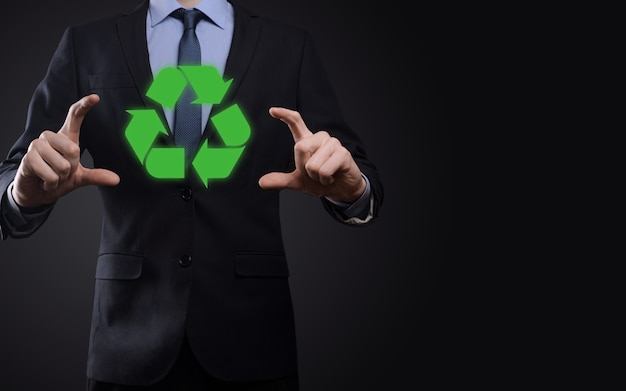 Hombre de negocios en traje sobre fondo oscuro tiene un icono de reciclaje, firme en sus manos. concepto de ecología, medio ambiente y conservación. luz azul roja neón