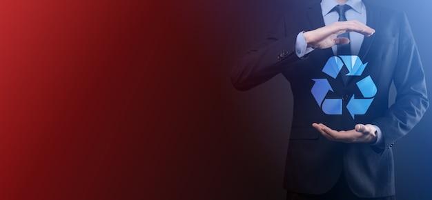 Hombre de negocios en traje sobre fondo oscuro tiene un icono de reciclaje, firme en sus manos. concepto de ecología, medio ambiente y conservación. luz azul roja neón.