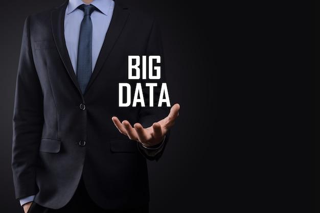 Hombre de negocios en un traje sobre un fondo oscuro tiene la inscripción big data. concepto de servidor en línea de red de almacenamiento representación de análisis de negocios o redes sociales.