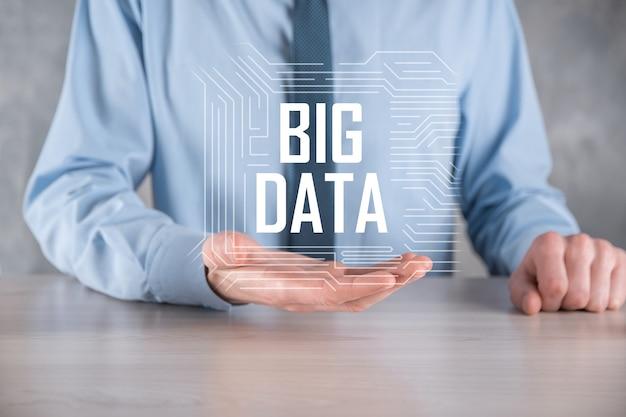 Hombre de negocios en un traje sobre un fondo oscuro tiene la inscripción big data. concepto de servidor en línea de red de almacenamiento.