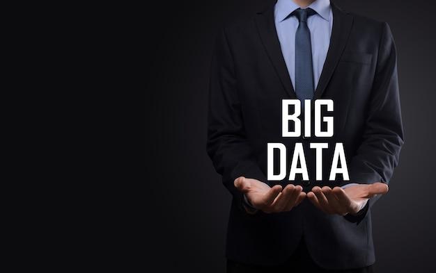 Hombre de negocios en un traje sobre un fondo oscuro tiene la inscripción big data. concepto de servidor de red de almacenamiento en línea representación de análisis de redes sociales o negocios