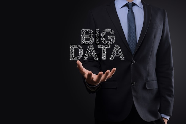 Hombre de negocios en un traje sobre un fondo oscuro tiene la inscripción big data