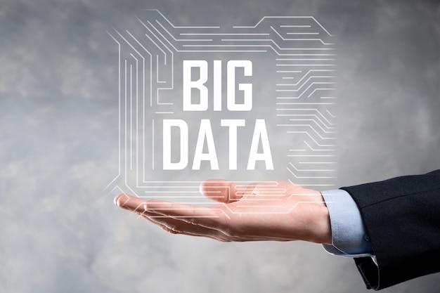 Hombre de negocios en un traje sobre un fondo oscuro tiene la inscripción big data.