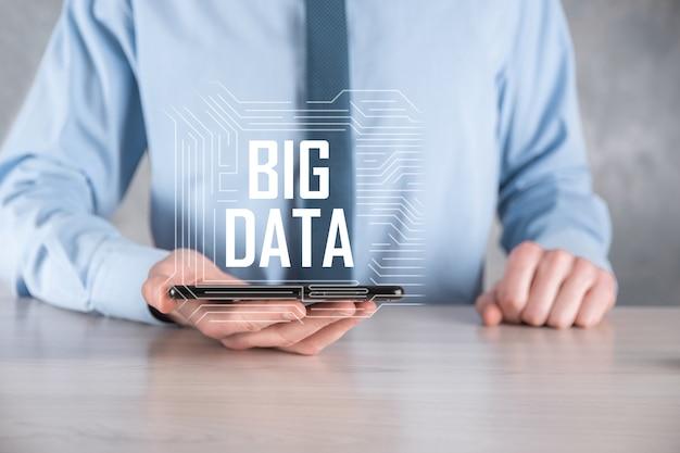 Hombre de negocios en un traje sobre una superficie oscura tiene la inscripción big data