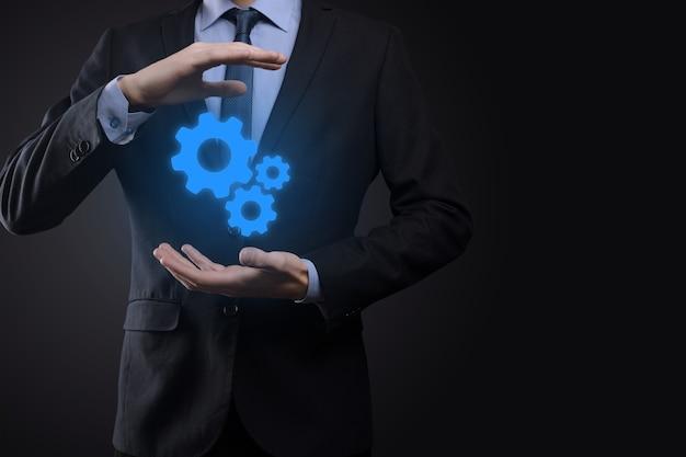Hombre de negocios en traje sosteniendo engranajes metálicos y mecanismo de ruedas dentadas que representa el concepto de trabajo en equipo de interacción, grupo de mano de rueda dentada virtual.